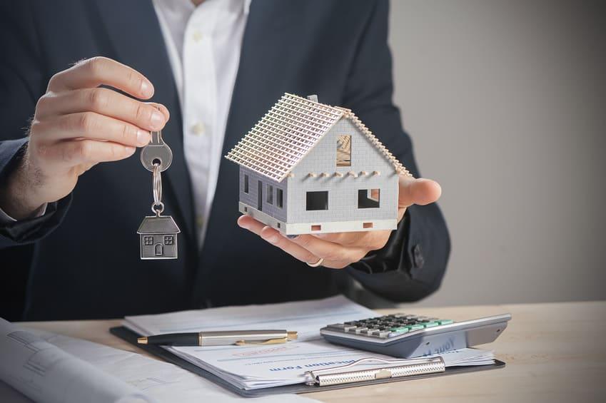 dom i klucze trzymane przez człowieka