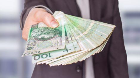człowiek trzymający pieniądze