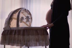kobieta w ciąży przy kołysce